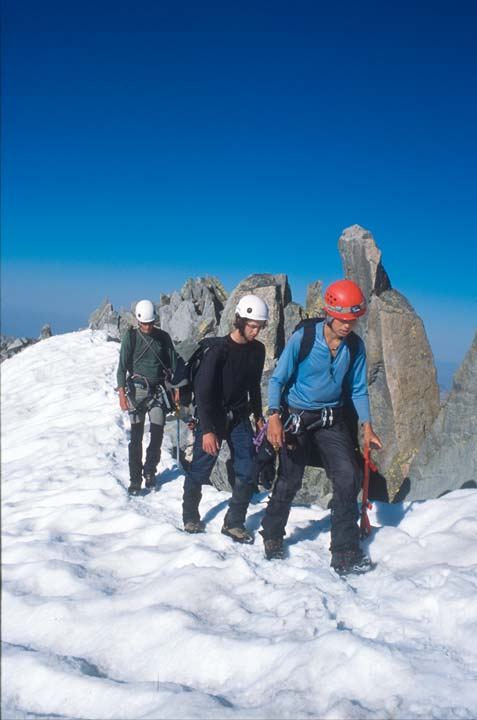 A trio of climbers navigate a snow covered alpine ridge, alongside a border of high rock pinnacles, under an empty blue sky.