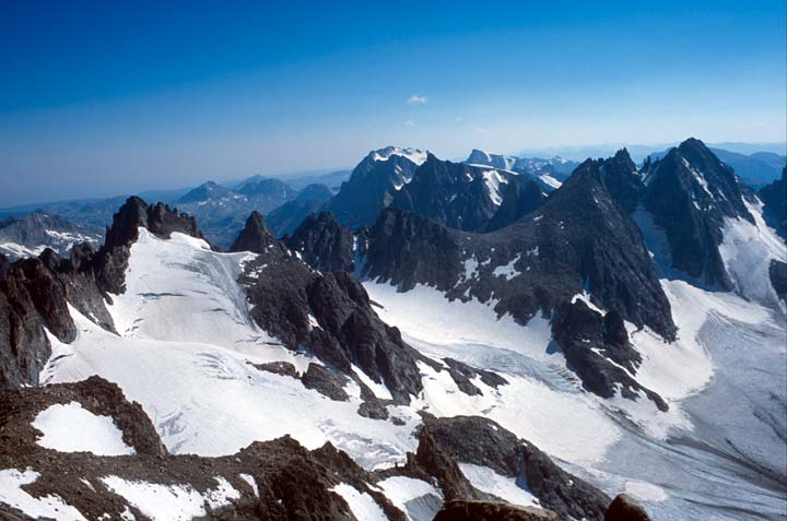 A harsh landscape of extreme jagged peaks and pinnacles, rising from hanging glaciers and snowpack, stretching away to the horizon.