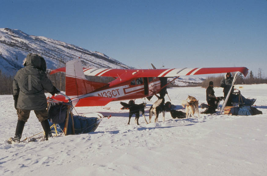 Three people standing around a sled and a small team of dogs, unloading supplies from a red aircraft on skis.