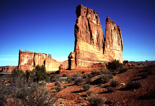 Two massive rock pinnacles rise like giant fins from the brown desert landscape, dotted with green brush.