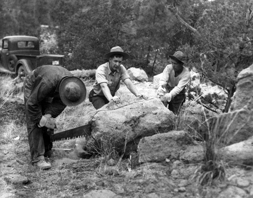A vintage black and white photograph of three men cutting a large rock in half, using a hand saw.