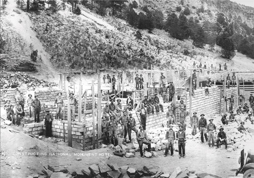 A vintage black and white photograph of a large operation with many men, cutting bricks from stone.