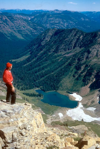 A man in a red jacket and hat, standing on a point, overlooking a small lake at the base of a forested valley far below.