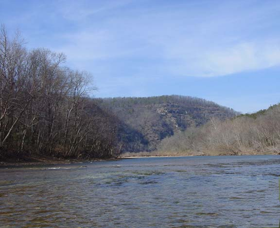 A small river bordered by gray woodland trees, flowing towards a high bluff in the distance.