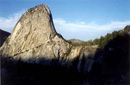 A massive rock pinnacle resembling a shark fin, looms over the forest below. Black shadows creeping up the base, drape the forest in darkness.