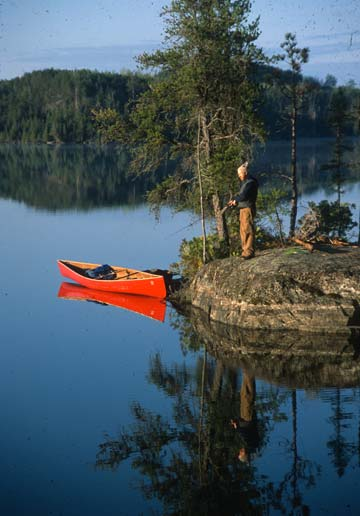 A tranquil scene of a man fishing from a small rock island, a bright red canoe tethered to a small tree nearby reflecting off the mirror surface of the water in evening light.