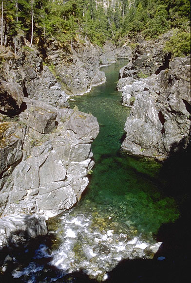 Looking down into a small narrow canyon, crystalline green water flowing through the middle.