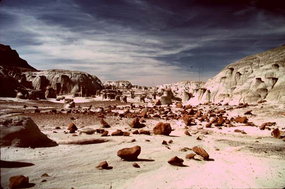 A seemingly Martian landscape of white sand littered with small brown boulders. Lumpy white cliffs rise in the background, under a black sky laced with wispy white clouds.