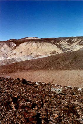 A desolate landscape of brown rock, cut by a large drainage mottled with gray clay.