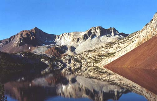 A tranquil scene of rugged mountains reflected from the mirror surface of an alpine lake, in various patterns of blues, browns, and grays.