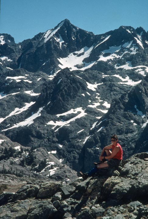 A woman in a red shirt sitting on a large rock, looking out across a valley to a jagged peak nearby, laced with summer snow.