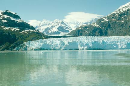 An Alaskan glacier framed by snow-covered mountains, as seen from the opposite side of a glacial Lake.