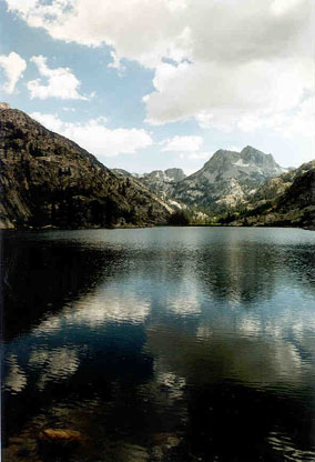 A large alpine lake, the mirror surface reflecting the surrounding snowcapped peaks.