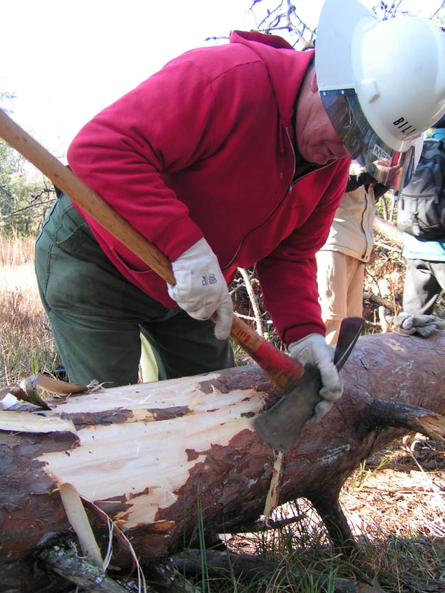 A man in a white hard hat, using an axe to scrape bark off a fallen tree.