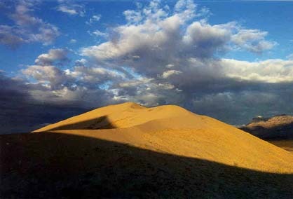 Golden sand dunes draped in rich evening light and striped with black shadow, under a blue sky mottled with cloud.