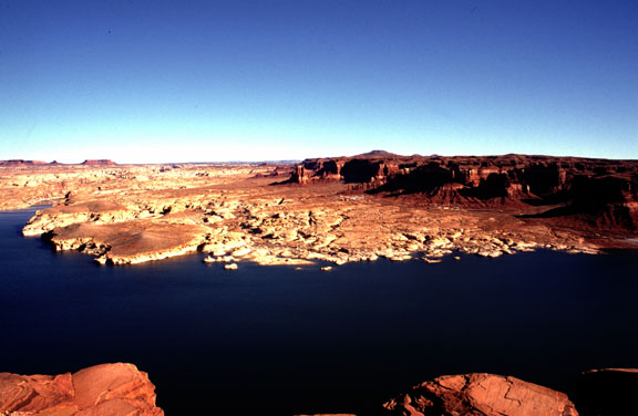 A red sandstone plateau divides blue sky above and deep blue water in the foreground.