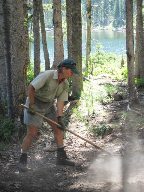 A woman using hand tools to restore the ground around the base of several large trees, along the edge of a small lake.