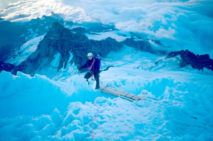 A lone hiker in full gear, high on a snow covered slope, far above the clouds swirling around jagged peaks and glacier ice below.