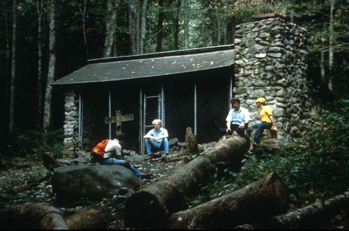 A small group of hikers, resting near a gated stone structure, in the forest.