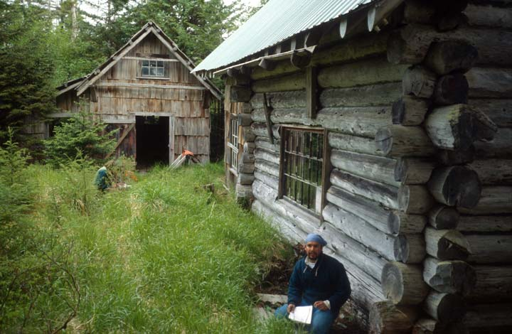 A man sitting in tall green grass, near the corner of an old log cabin.