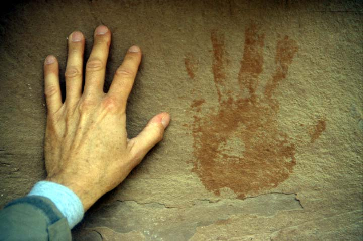 A hand, held next to an ancient pictograph of a brown handprint on a stone face.