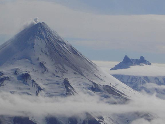 The Shishaldin and Isanotski volcanes are blanketed in snow and thin clouds scuttle about them as they stand silently.