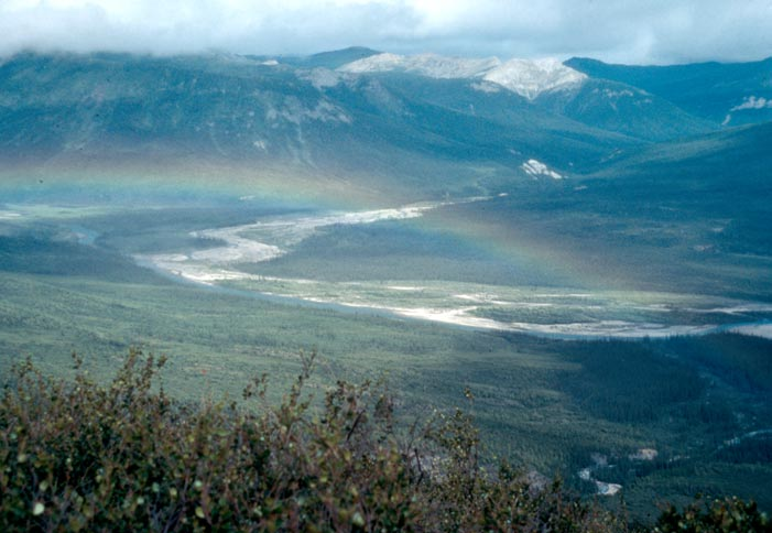 A rainbow stretching over a large river valley in the arctic tundra, with low mountains rising beyond.