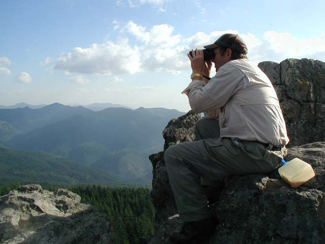 Male hiker sitting on a rock watches wildlife in the distance through binoculars.