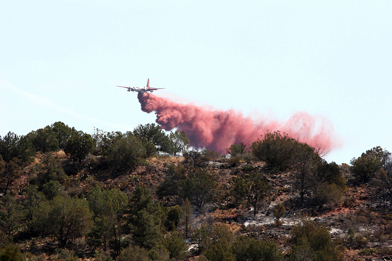 A plane drops fire retardant on a fire